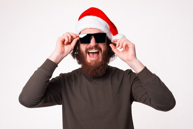 Excited bearded man is wearing christmas hat and a pair of sunglasses.
