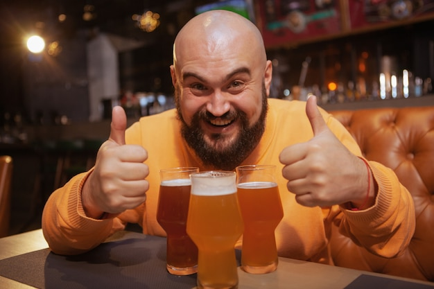 Excited bearded man laughing, showing thumbs up sitting in front of three beer glasses at the pub