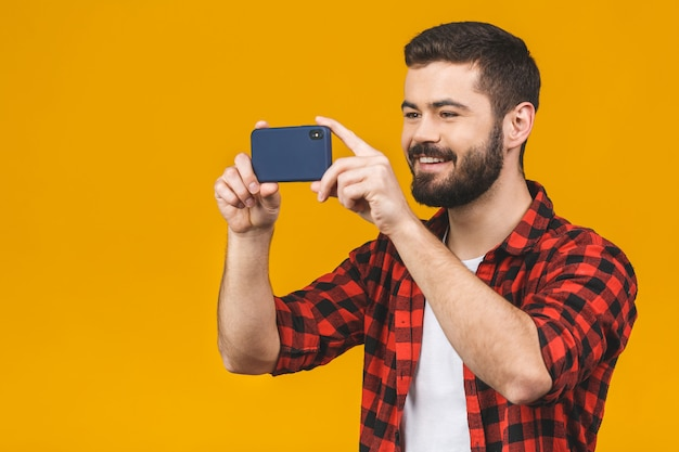 Excited bearded man in plaid shirt playing on smartphone isolated over yellow wall.