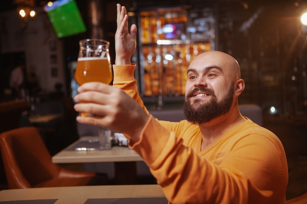 Excited bearded man praising his beer. happy man looking with love at the beer glass he is holding