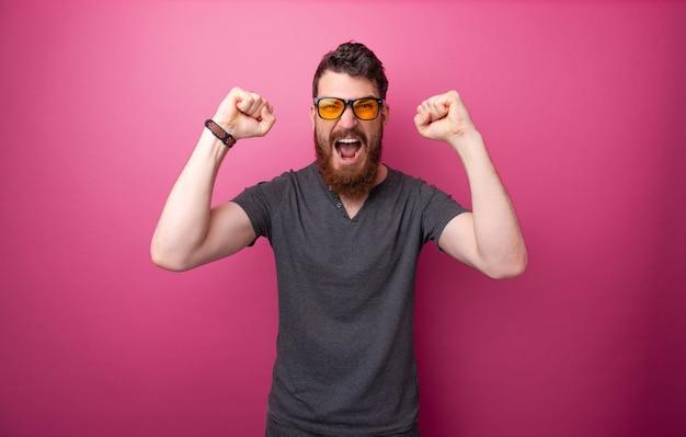 ピンクの背景の上に立って、上げられた手で叫び、祝う、興奮したひげを生やした男