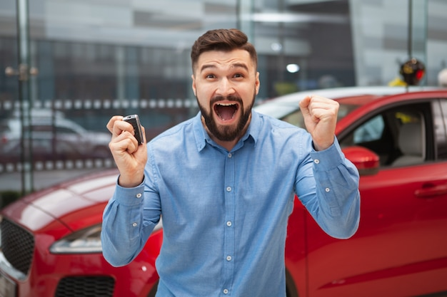 Excited bearded man screaming happily, holding car keys to his new automobile.