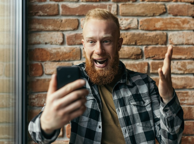 Excited bearded man using mobile phone, watching football online, sport betting, celebration success