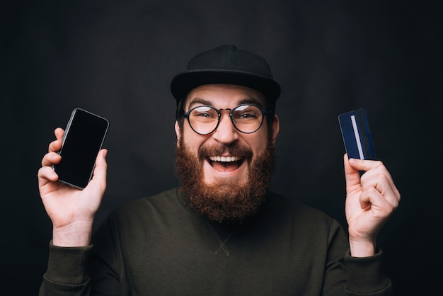 Excited bearded man wearing glasses and cap is holding a card and his phone.