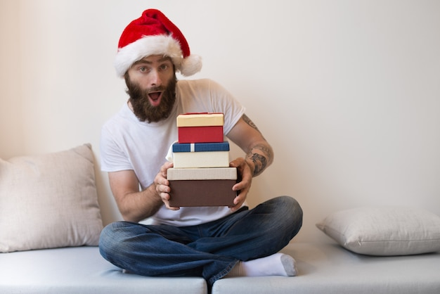 Excited bearded man wearing santa hat and holding gift boxes