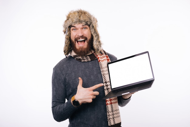 Excited bearded man wearing winter warm hat or cap, a scarf is poiting at his blank white screen laptop.