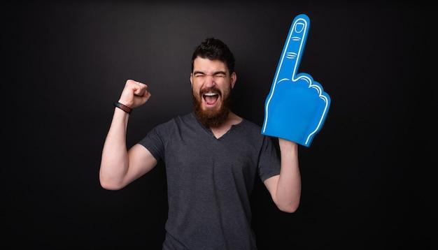 큰 파란색 장갑을 낀 흥분한 수염 난 남자, 어두운 배경 위에 손을 들고 비명을 지르고 축하