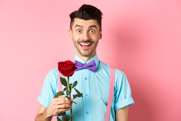 Excited bearded man with moustache and bow-tie waiting for date with red rose