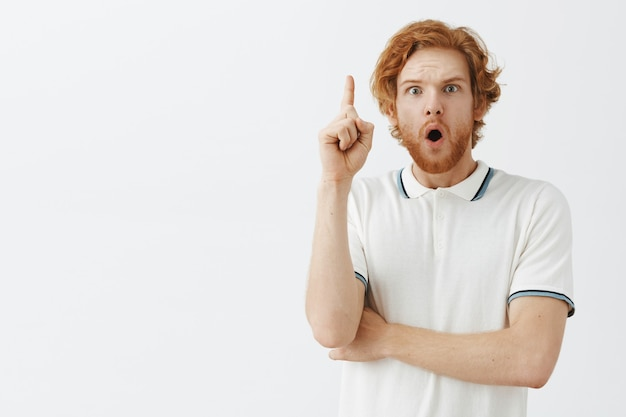 Excited bearded redhead guy posing against the white wall