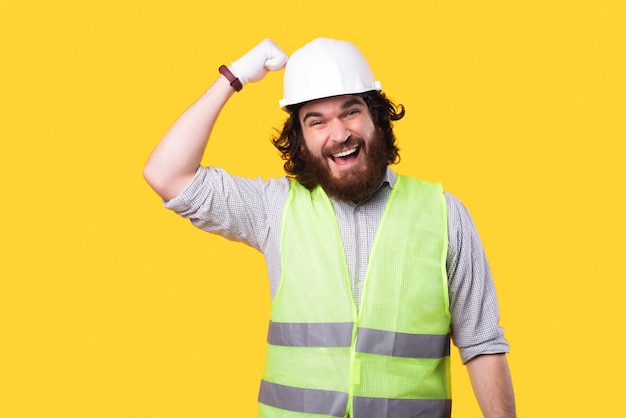 Excited bearded and young engineer is looking at the camera and is beating in the helmet thats on his head near a yellow wall