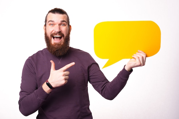 Excited bearded and young man is holding a speech bubble and is looking at the camera with his mouth opened