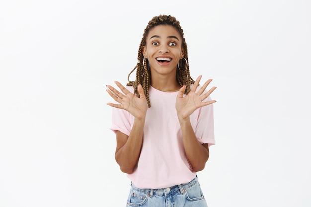 Возбужденная красивая афро-американская девушка улыбается изумленно, рассказывая важные новости