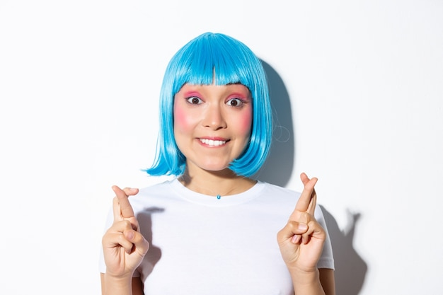 Excited beautiful asian girl in blue wig biting lip and looking hopeful at camera