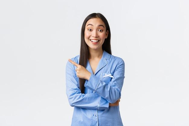 Возбужденная красивая азиатская девушка в синей пижаме, указывая пальцем влево и восторженно улыбаясь, показывает потрясающий промо-баннер, рассказывает о продукте, делает объявление на белом фоне.