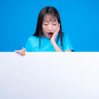 Excited beautiful asian young woman with bangs hair style in blue t shirt smiling and looking a blank space for advertising banner , empty space white board a blank banner isolated on blue background