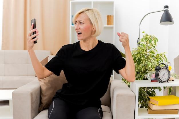 Bella donna russa bionda emozionante si siede sulla poltrona mantenendo il pugno e guardando il telefono