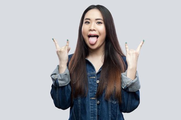 カジュアルな青いデニムジャケット、メイクアップ立って、岩の手と舌でカメラを見て興奮した美しいブルネットのアジアの若い女性。明るい灰色の背景に分離された屋内スタジオショット。