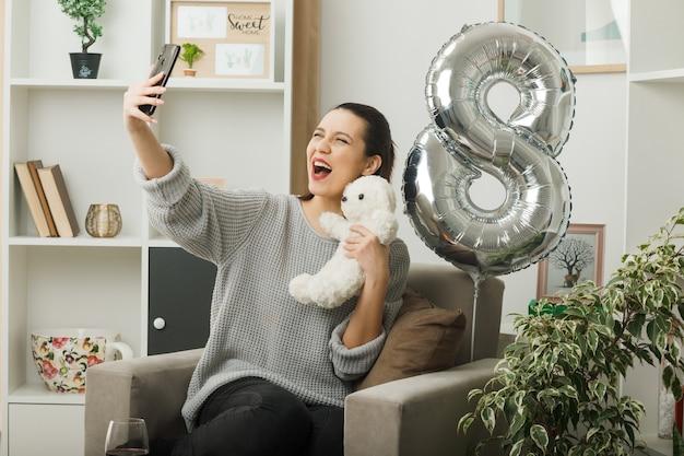 Bella ragazza eccitata durante la giornata delle donne felici che tiene in mano un orsacchiotto, si fa un selfie seduto sulla poltrona in soggiorno