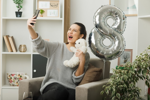 テディベアを保持している幸せな女性の日に興奮した美しい少女は、リビングルームのアームチェアに座って自分撮りを取ります