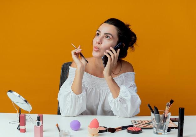 Взволнованная красивая девушка сидит за столом с инструментами для макияжа и разговаривает по телефону, держа кисть для макияжа, глядя вверх изолированно на оранжевой стене