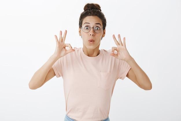 白い壁にポーズをとってメガネで興奮した美しい少女