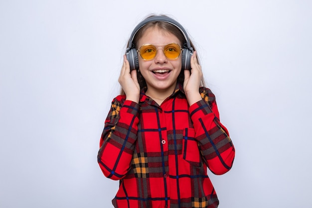Excited beautiful little girl wearing red shirt and glasses with headphones isolated on white wall