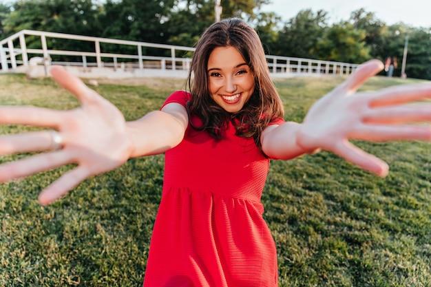 Возбужденная красивая белая девушка позирует в парке. эмоциональная хорошо одетая дама весело на открытом воздухе.