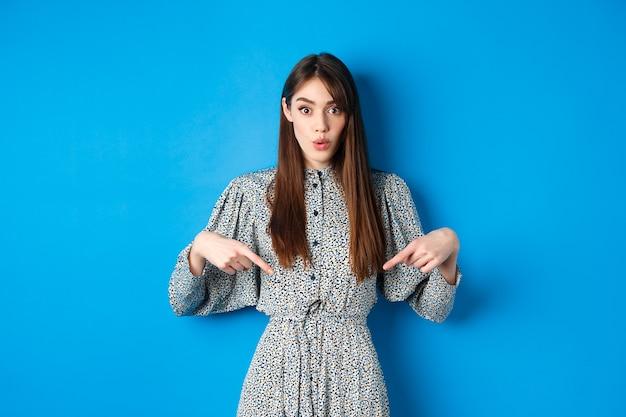Возбужденная красивая женщина в платье говорит «вау», указывая пальцами вниз и выглядит удивленным, проверяя продвижение по службе, стоя на синем.