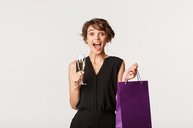 우아한 복장, 샴페인을 마시고 선물 가방을 들고, 뭔가를 축하하고, 흰색 위에 서있는 아름 다운 여자를 흥분.