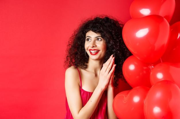 곱슬 머리를 가진 흥분된 아름다운 여성, 심장 풍선 근처에 서서 손바닥을 함께 문지르는 것은 좋은 거래 또는 맛, 빨간색 배경을 기대합니다.