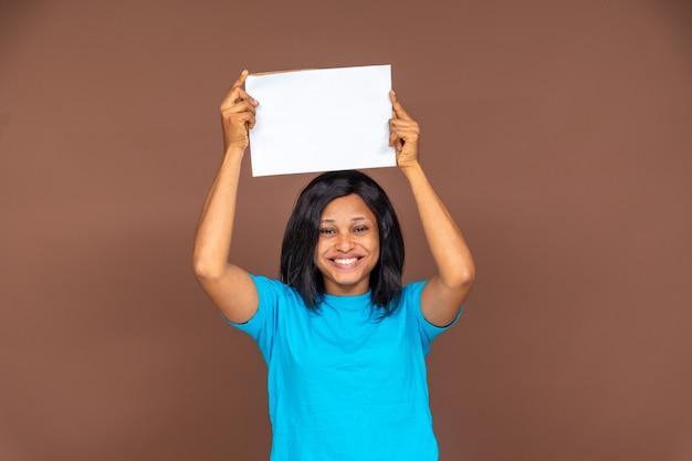 Возбужденная красивая молодая африканская дама держит пустой знак, рекламная концепция