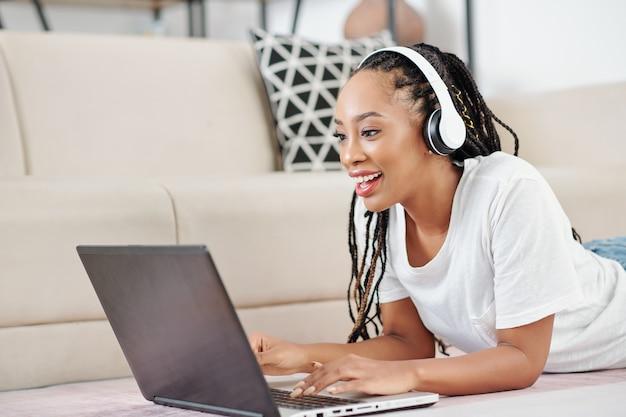 험 상을 바닥에 누워 공부하거나 랩톱에서 작업하는 흥분된 아름다운 젊은 흑인 여성