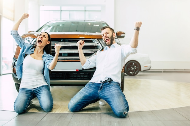 Excited beautiful young family in the dealership after buying a car