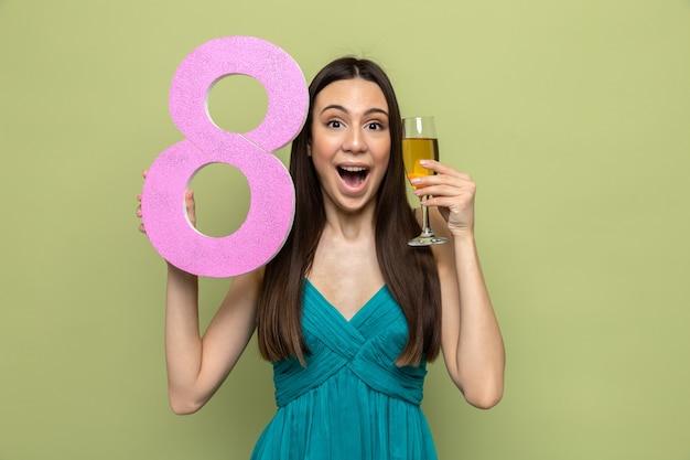 オリーブグリーンの壁に隔離された顔の周りにシャンパングラスで8番を保持している幸せな女性の日に興奮した美しい少女