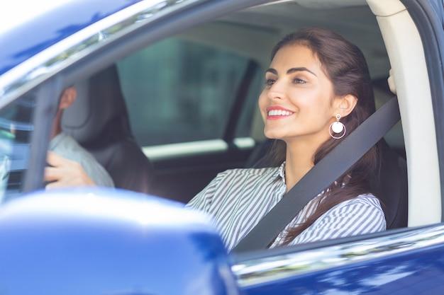 Возбужден перед поездкой. подруга в полосатой блузке взволнована перед вождением машины мужа