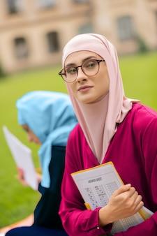 講義の前に興奮しました。講義の前に興奮している眼鏡をかけている美しいイスラム教徒の学生