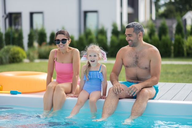 Возбужден перед купанием. веселая блондинка дочь чувствует себя взволнованной перед плаванием в бассейне с родителями