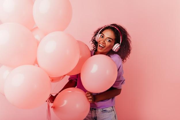 풍선과 함께 포즈를 취하는 큰 헤드폰에 흥분된 생일 소녀. debonair 아프리카 아가씨 파티에서 듣는 음악.