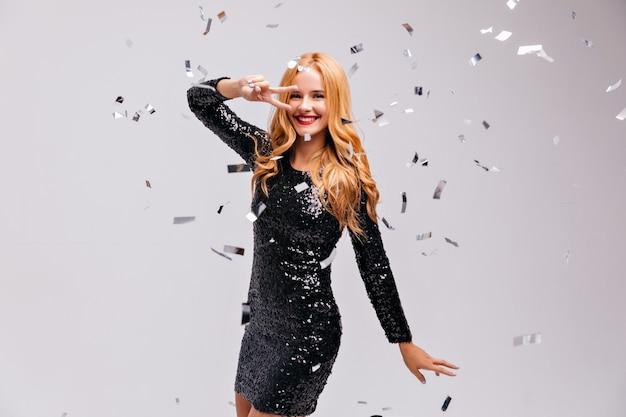 평화 서명 포즈와 웃음 흥분된 생일 소녀. 스파클 검은 드레스에 jocund 유럽 아가씨의 총.