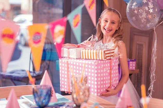 Взволнованная именинница улыбается, держа в руках большие подарки