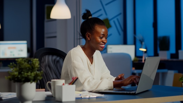 Excited black freelancer smiling while reading good news on laptop working overtime in start up company office. enthusiastic employee owerworking late night respecting deadline of financial project