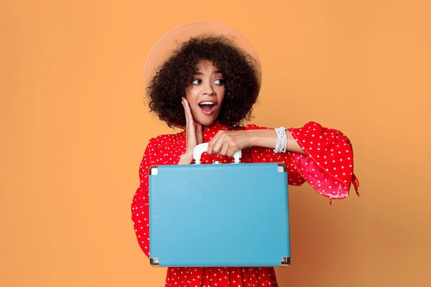 Excited  black girl with african hairstyle holding cute blue suitcase.