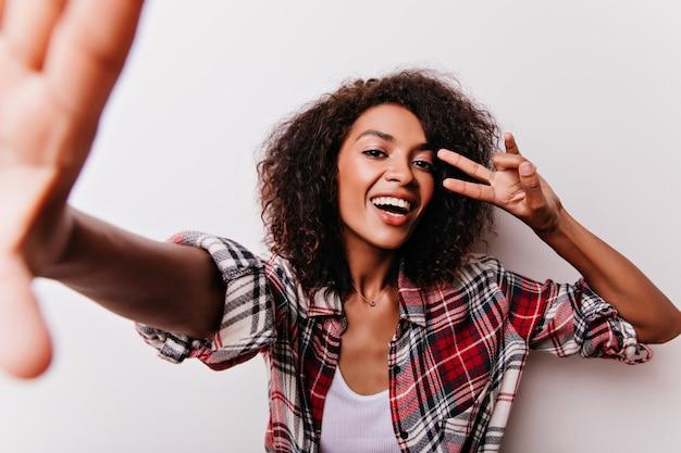 Возбужденная черная девушка с короткой прической развлекается на белом. восторженная красивая женщина в красной рубашке.