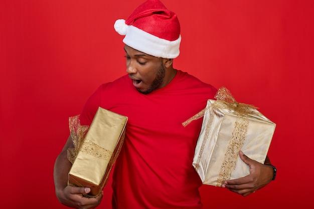 Взволнованный темнокожий мужчина в шляпе санта-клауса держит обернутые подарочные коробки под мышками на красном фоне