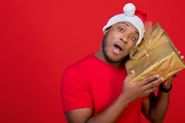 サンタクロースの帽子をかぶった興奮した黒人男性が、中身が何であるか疑問に思ってパックされたギフトボックスを振る