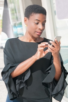 Excited black woman dialing number on mobile phone