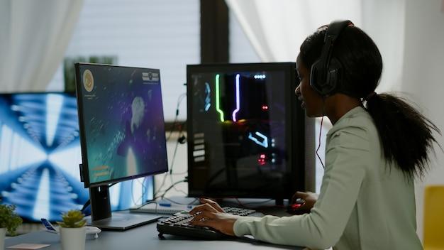 机の上に座って、マイク付きのヘッドセットを持っている興奮した黒人女性ゲーマーがスペースシューティングビデオゲームをプレイしています。ゲームトーナメント中に強力なパーソナルコンピュータで実行するオンラインストリーミングサイバー