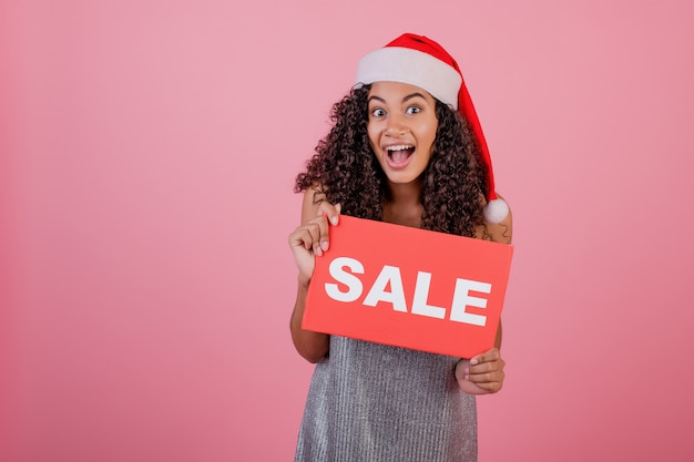 Excited black woman holding copyspace red sale sign and wearing santa hat isolated over pink