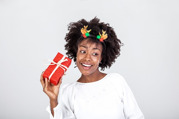 Excited black woman shaking wrapped gift box receiving presents on her birthday or christmas standing