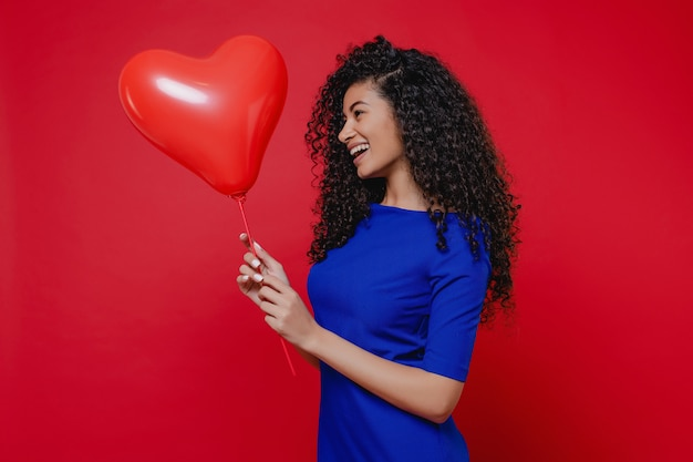 Excited black woman with heart shaped balloon wearing blue dress on red wall
